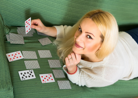 predictor: Relaxed smiling woman lying on a sofa at home laying out cards trying to predict future