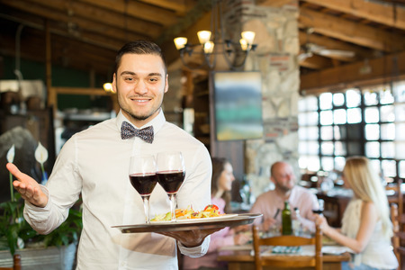 Cheerful smiling young male waiter serving restaurant guests Stock Photo
