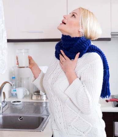 antiseptic: young blonde with scarf gargling at kitchen