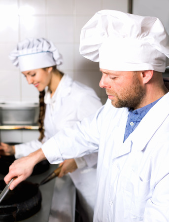 house robes: Chef and cook  working at take-away restaurant kitchen