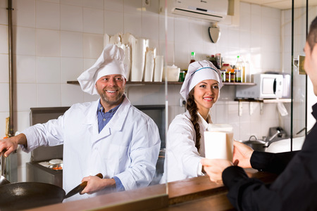 house robes: Smiling customer, chef and cook at fastfood place Stock Photo