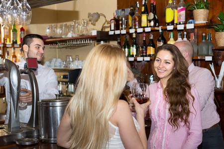 barman: Happy friends drinking and chatting with barman at bar counter