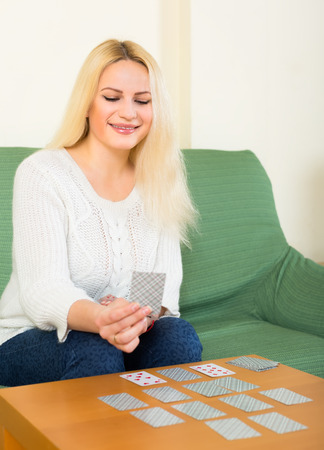 Happy young blonde sitting on a couch by the table and playing a solitaire card game