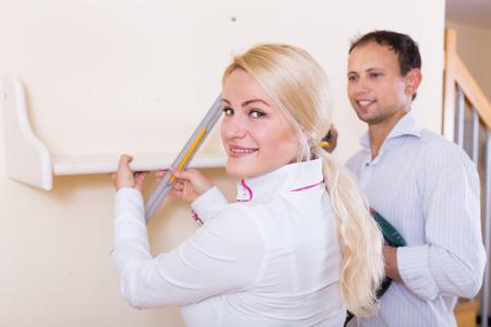 modifying: happy russian couple hangs bookshelf on a wall Stock Photo