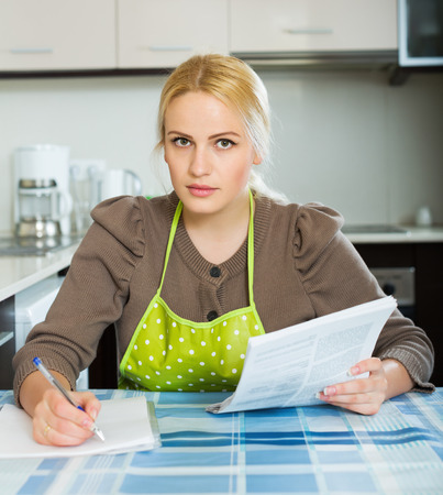 speculate: Serious blonde woman reading document at kitchen Stock Photo