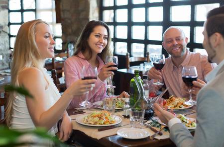 Portrait of smiling young adults having dinner in family restaurant. Focus on brunette girl Standard-Bild