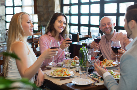 Portrait of smiling young adults having dinner in family restaurant. Focus on brunette girl Stock Photo