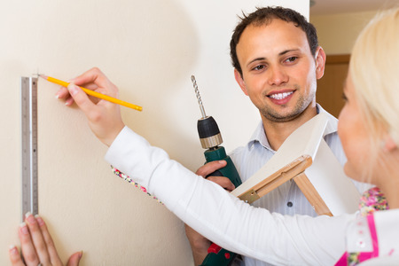modifying: Smiling young  married couple  makes repairs together at home Stock Photo