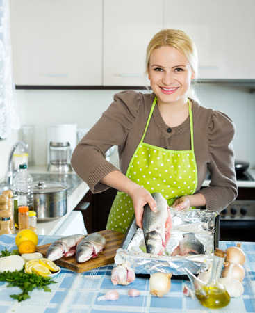 cook griddle: Happy blonde girl cooking fish  in frying pan at home kitchen