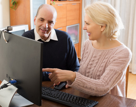 happy old people: Senior couple talking with someone online and smiling Stock Photo