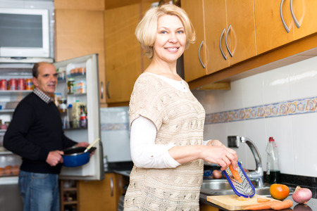 elderly: Portrait of senior couple cooking in the kitchen. Beautiful elderly woman is grating carrots while her husband is taking a pan from an opened refridgerator Stock Photo