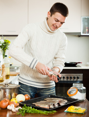 panful: Handsome man adding spices in fish on baking sheet at home kitchen Stock Photo
