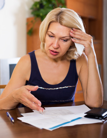 financial questions: Portrait of sad blond woman reading utility payments at the table indoor Stock Photo