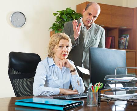 patron: Protuberancia enojada que grita en su asistente femenina madura en la oficina Foto de archivo