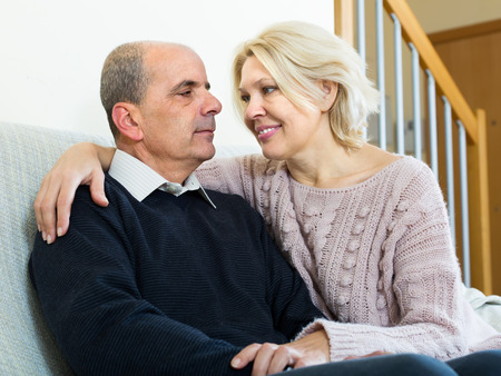 gladful: Senior loving husband and wife cuddling on couch at home Stock Photo