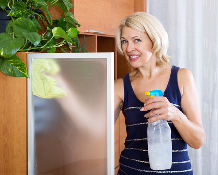 dusting: Smiling woman dusting glass of furniture at home
