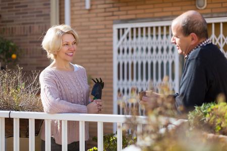 발콘에서 남성 이웃과 대화 성숙한 웃는 여자