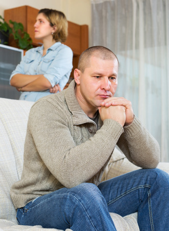 unhappy man: Family quarrel. Upset man against unhappy young woman at home
