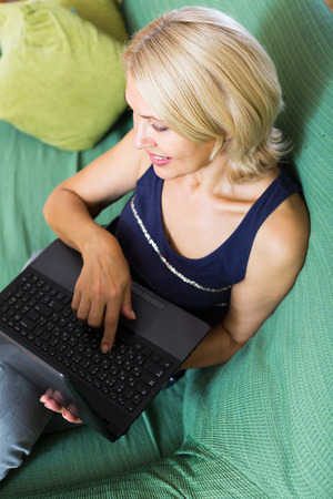 50 to 60 years: smiling mature woman using computer on sofa in home