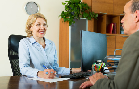 bank manager: Elderly man talking with bank manager about opening saving account