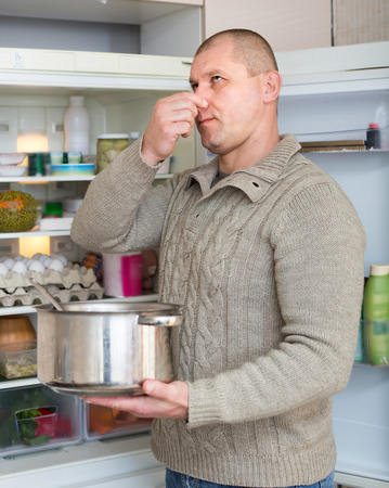 frowy: Hungry man holding foul food near refrigerator at home Stock Photo