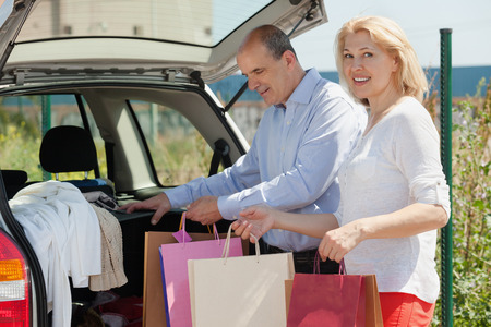 novelties: Smiling senior spouses with bags near car at shopping center