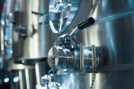 stell: contemporary winery with  stell barrels. Focus on valve of pipes