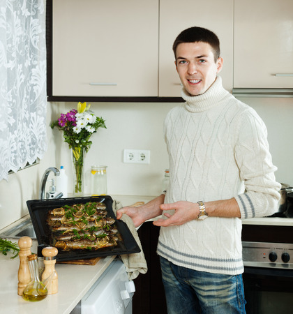 fryingpan: Smiling man with cooked fish on  frying pan at home  kitchen
