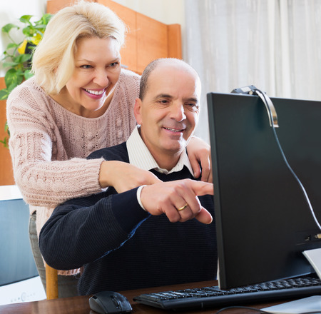 global retirement: Happy elderly couple talking with someone online and smiling at home