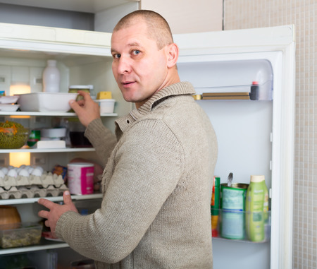 starving: Man caught standing near opened refrigerator searching for a meal