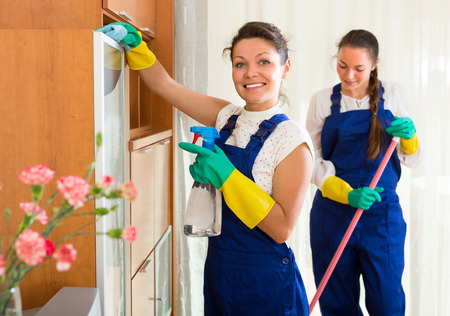 cleaning team: Professional cleaners team cleaning in the house with rags and mop and smiling. Selective focus