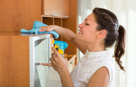 atomizer: Young brunette woman cleaning furniture at home with atomizer and rag