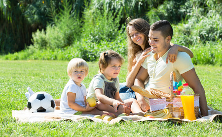 Happy family of four having picnic at meadow. Focus on man