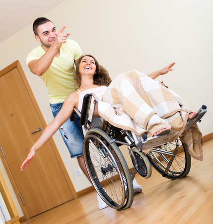 invalidity: Excited girl in wheelchair playing with her friend in home interior