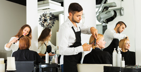 Hairdresser cuts young girl's hair in the beauty salon Foto de archivo