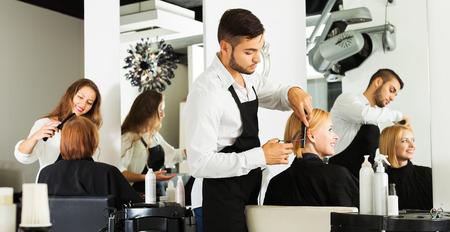 hair dryer: Peluquer�a corta el pelo de la chica joven en el sal�n de belleza Foto de archivo