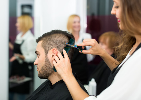 hairtician: Professional hairdresser is making a haircut with scissors and a comb for a male customer Stock Photo