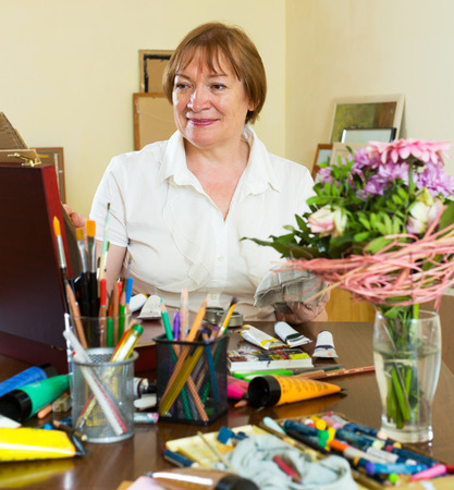 contentedness: Smiling adult woman painting a new picture