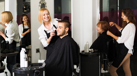 ordinary woman: Hairdresser makes the cut for man in the hairdressing salon Stock Photo