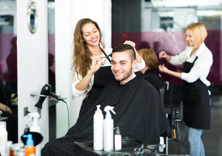 Beautiful hairdresser making a stylish haircut with sharp scissors for a man in a hair studio Stock Photo