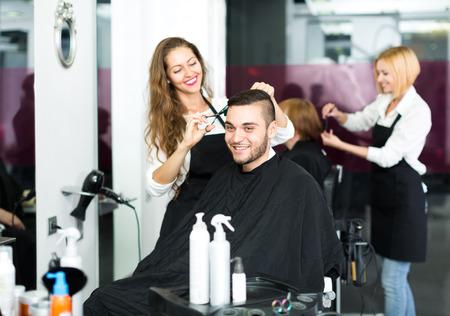 estilista: Peluquero hermoso hacer un corte de pelo con estilo, con unas tijeras afiladas para un hombre en un estudio del pelo Foto de archivo