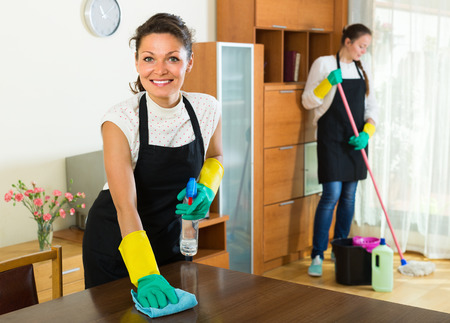 Two cheerful smiling girls in aprons cleaning together in the room