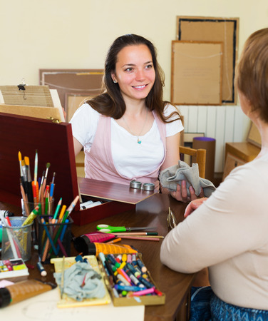 female likeness: Smiling young girl paints a portrait of a mature woman