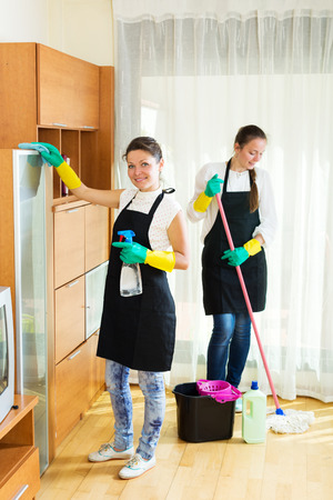 company premises: Smiling young women workers cleaning company ready to start work