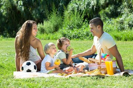 family of five: Happy smiling parents with little daughters having holiday with picnic at park