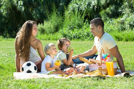 familia pic nic: Happy sonrientes padres con hijas peque�as que tienen vacaciones con picnic en el parque Foto de archivo