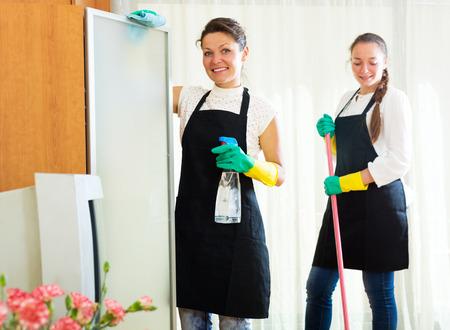 Sonriendo mujeres trabajadores listos para empezar a trabajar empresa de limpieza Foto de archivo