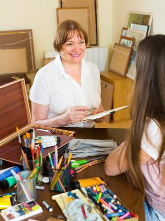 sitter: Smiling mature female artist painting portrait of longhaired girl at art studio