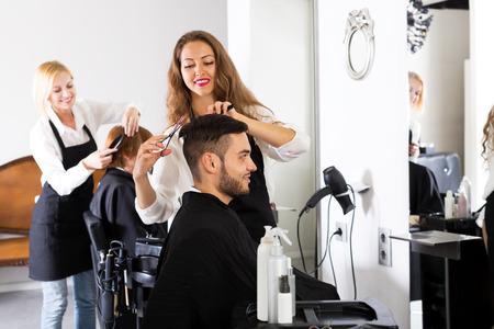 barbero: Individuo feliz corta el pelo y peluquer�a femenina en la peluquer�a. Centrarse en el hombre