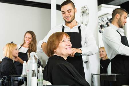 haircutter: barber makes the cut for adult woman